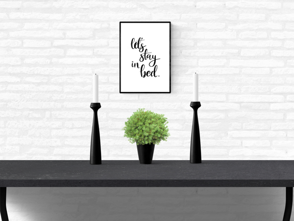 "Framed wall quote typography print with the words ""let's stay in bed"", mounted on a home's interior white brick wall above a table"