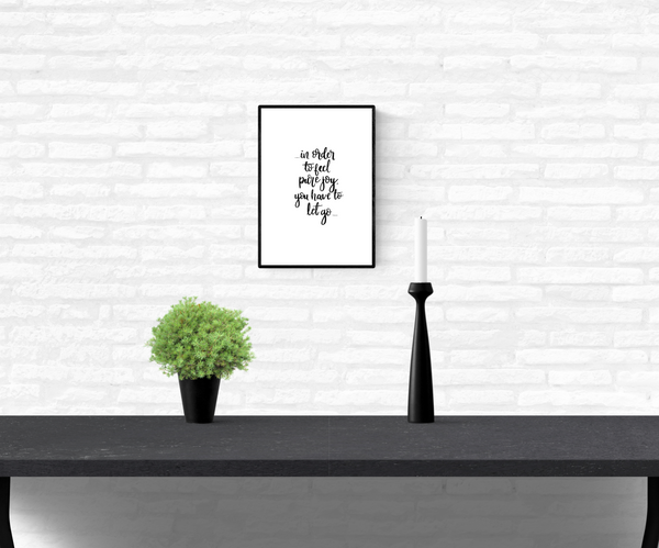 "Wall quote print with the words, ""in order to feel pure joy you have to let go"", framed and mounted on a home's interior white brick wall"