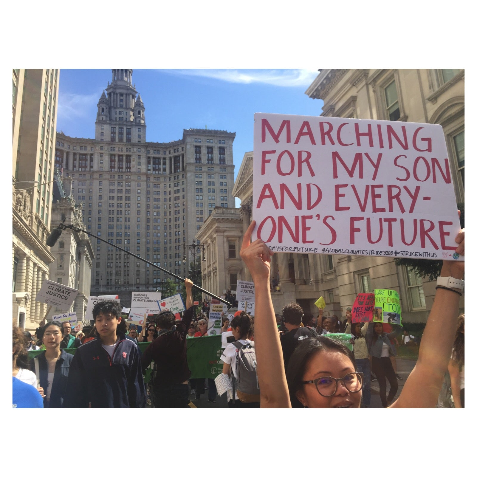 "A woman holds up a sign during the New York climate strike that says, ""Marching for my son and everyone's future""."