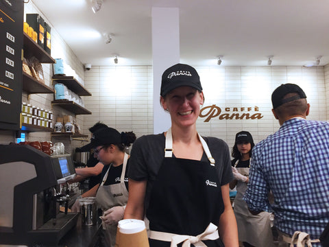 The female head chef wears a black baseball cap and black BoWorkwear apron as she smiles at the camera.