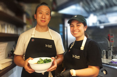 A man and a woman, both wearing a baseball cap and black aprons smile at the camera. The man holds a white bowl filled with beef noodle soup.