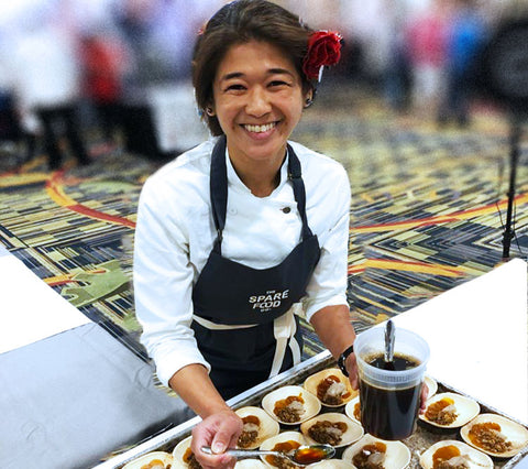 A young woman wearing a dark colored apron smiles at the camera as she plates food in small compostable bowls.