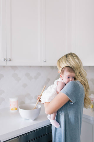 A Majka mama holding her baby and making a snack.