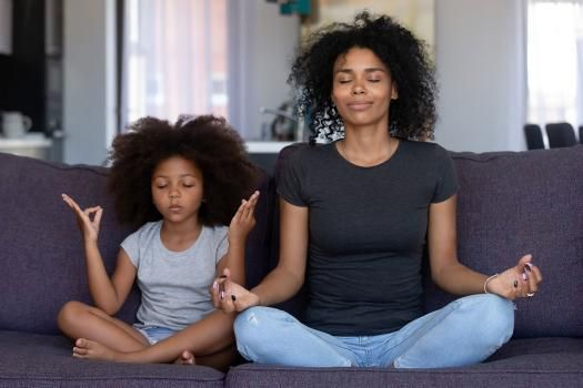 Mom and daughter sitting in yoga position
