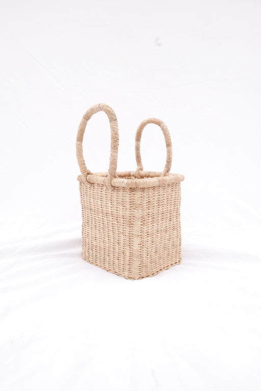 The Fuseini handbag is handwoven with straw called Kinkahe in Bolgatanga, Ghana. The shape is cube-like with two handles for durability. This product supports a community with employment, educational opportunities for the children and improve the work environment.
