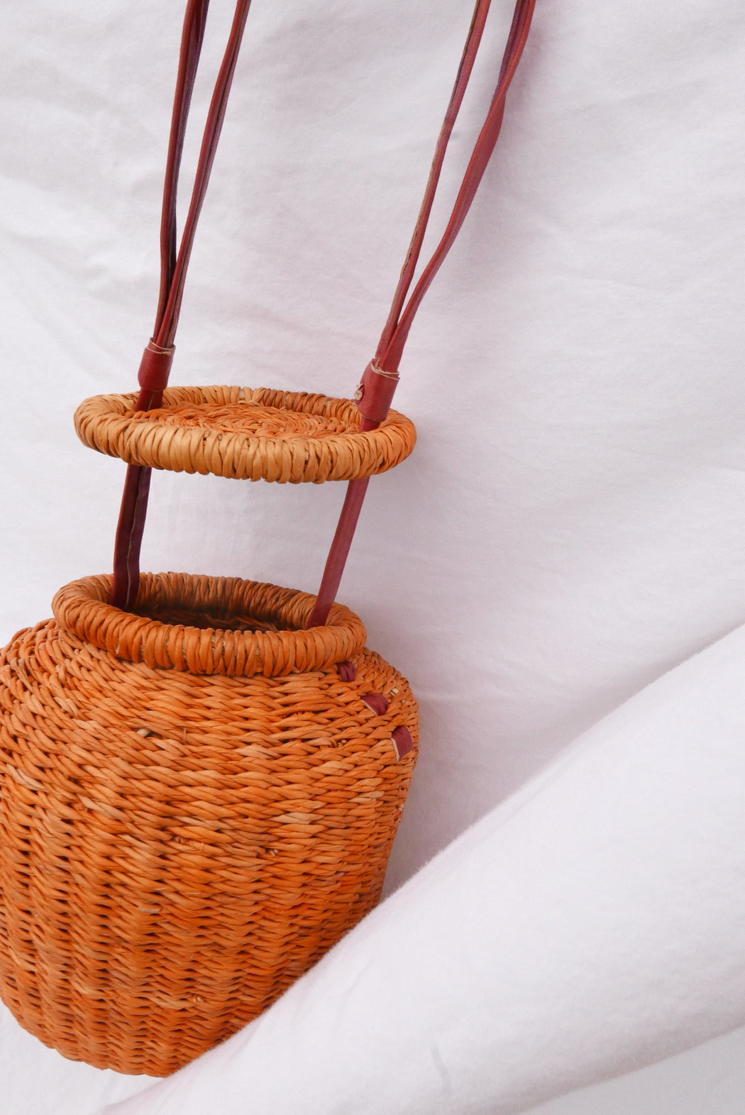 The orange Alobahe handbag is handwoven with straw called Kinkahe in Sherigu, Ghana. The shape is versatile and opens from the lid lifted vertical with an adjustable leather strap that can be worn as a crossbody or a handheld bag. This product supports a community with employment, educational opportunities for the children and improve the work environment.