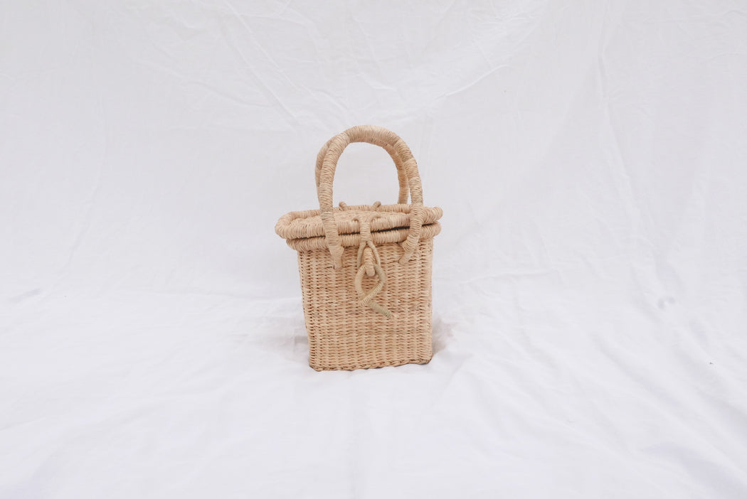 The Ayinberi handbag is handwoven with straw called Kinkahe in Bolgatanga, Ghana. The shape is cube-like with a lid and clasp to close and two handles for durability. This product supports a community with employment, educational opportunities for the children and improve the work environment.