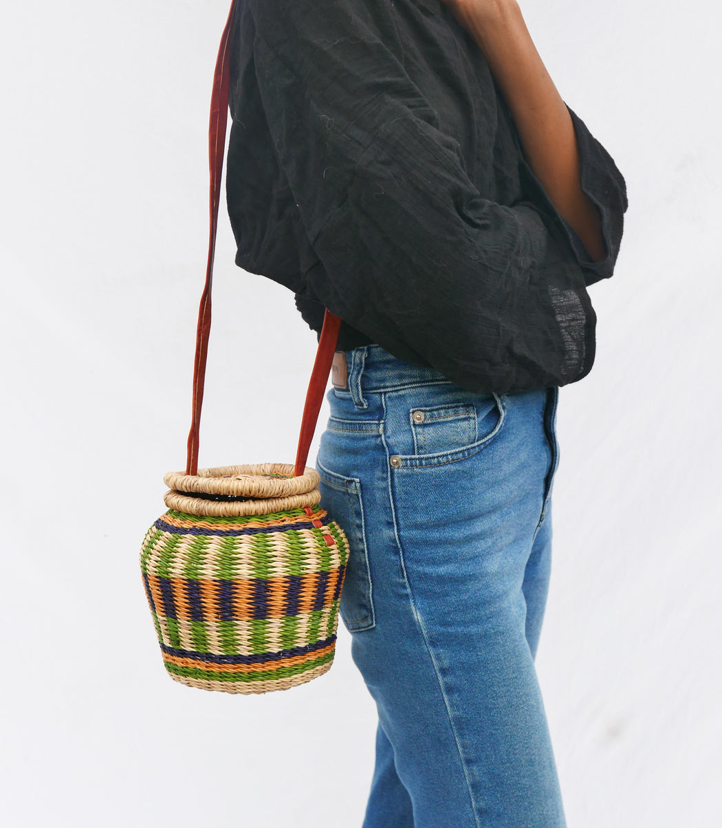 The multicolored Alobahe handbag is handwoven with straw called Kinkahe in Sherigu, Ghana. The shape is versatile and opens from the lid lifted vertical with an adjustable leather strap that can be worn as a crossbody or a handheld bag. This product supports a community with employment, educational opportunities for the children and improve the work environment.
