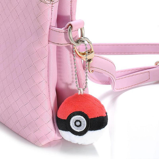 pokemon pokeball plush keychain attached to a pink handbag