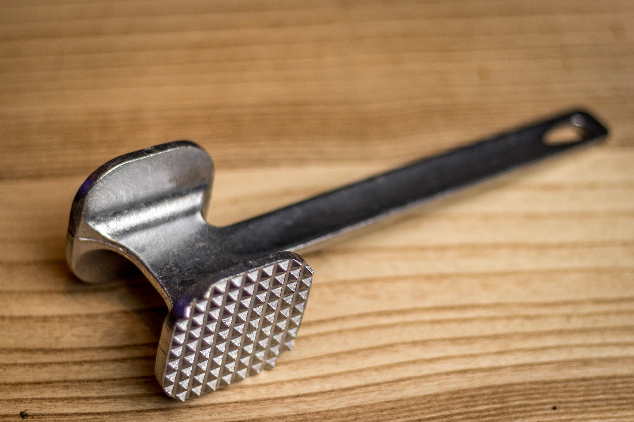 Stainless steel double-sided meat tenderizer.