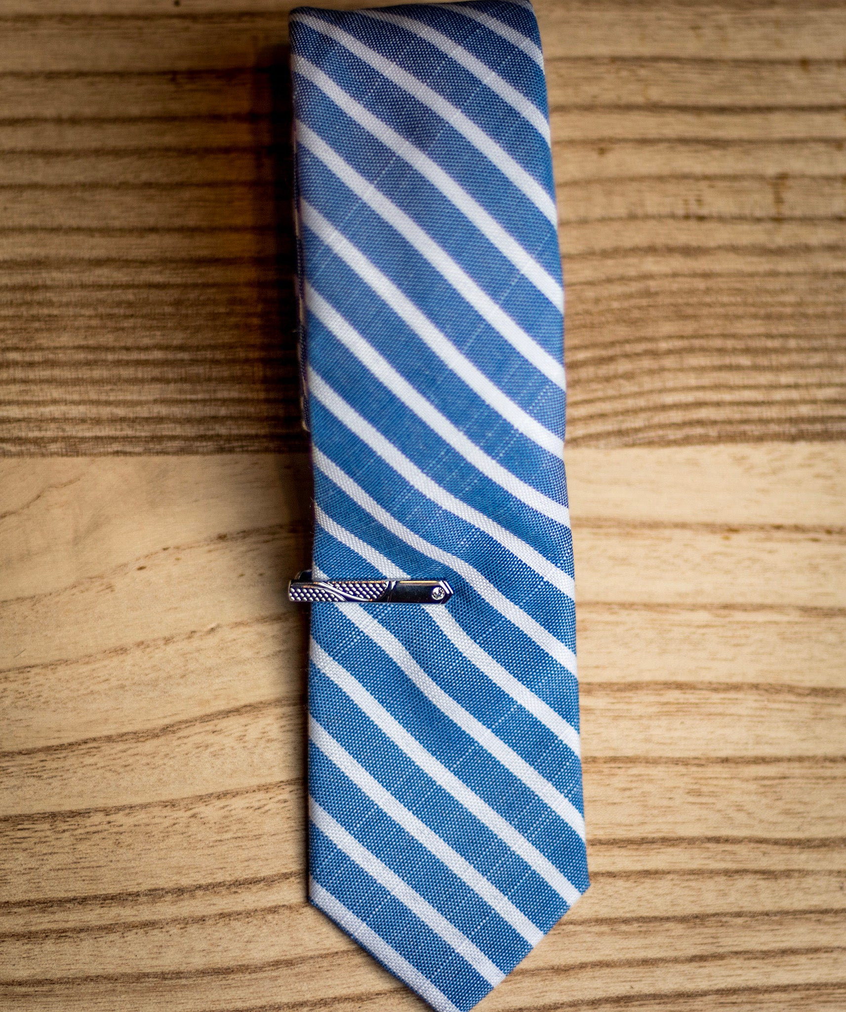 Blue cotton skinny tie with matte finish tie clip.