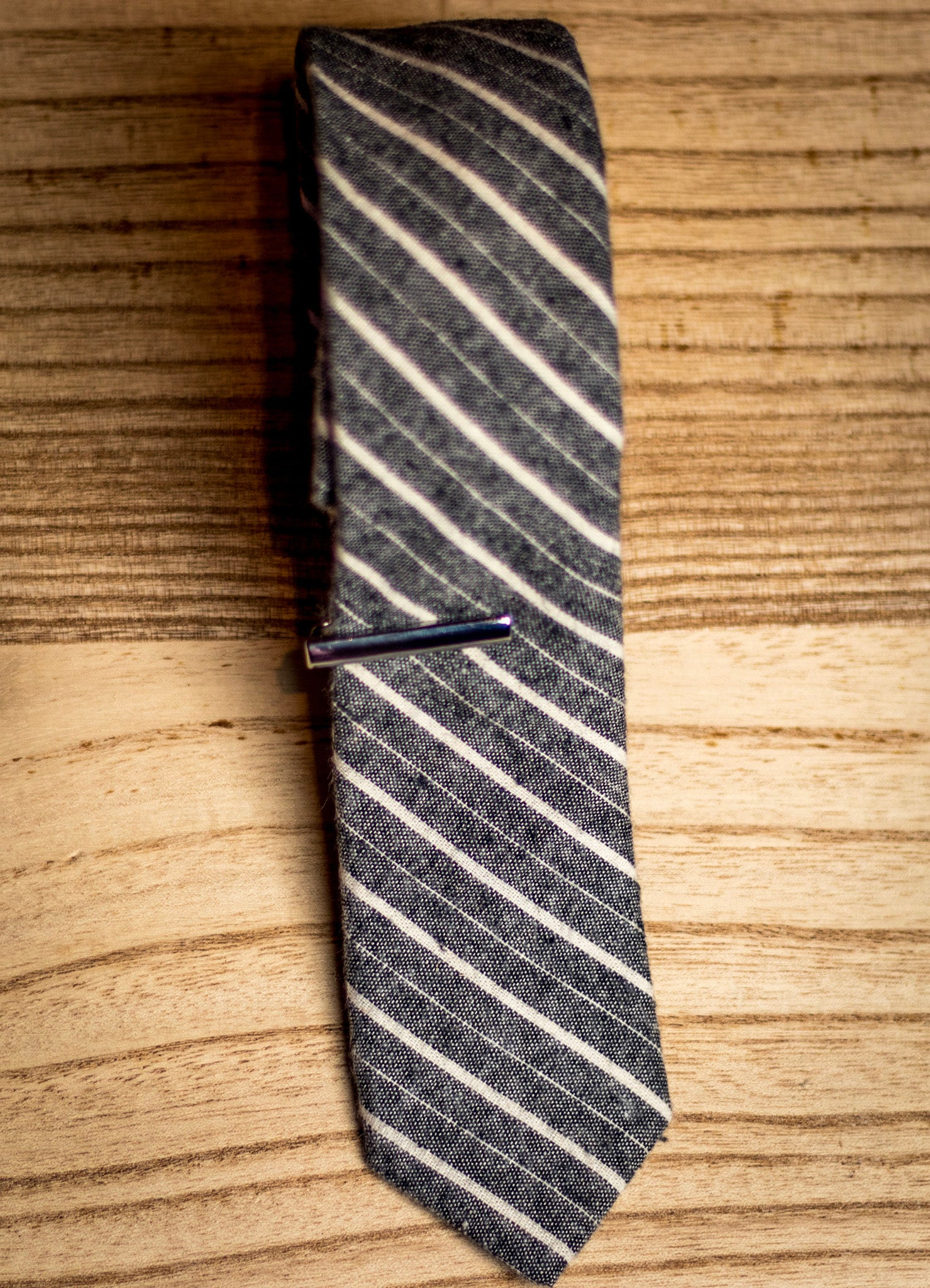 Gray cotton tie with matte finish metal tie clip.