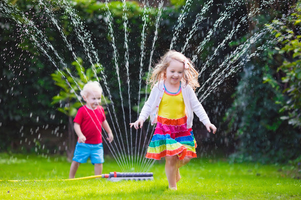 Kids running through sprinkler