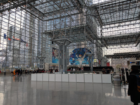 Inside the Jacob K. Javits Convention Center, also known as the Crystal Palace. Fate Stay Order posters are up and videos are playing in the background.