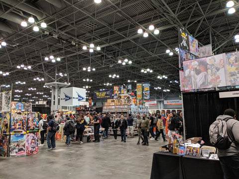 Wide shot of the inside of the Anime NYC 2018 exhibit hall. Large crowd of people around various anime and manga merchandise booths.