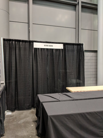 Empty booth at Anime NYC 2018. Simple black curtain wall in the back, with a placeholder sign for Katana Sakana. We were given three empty tables with black table cloths.