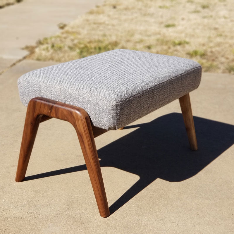 Hand sculpted walnut ottoman with grey fabric.