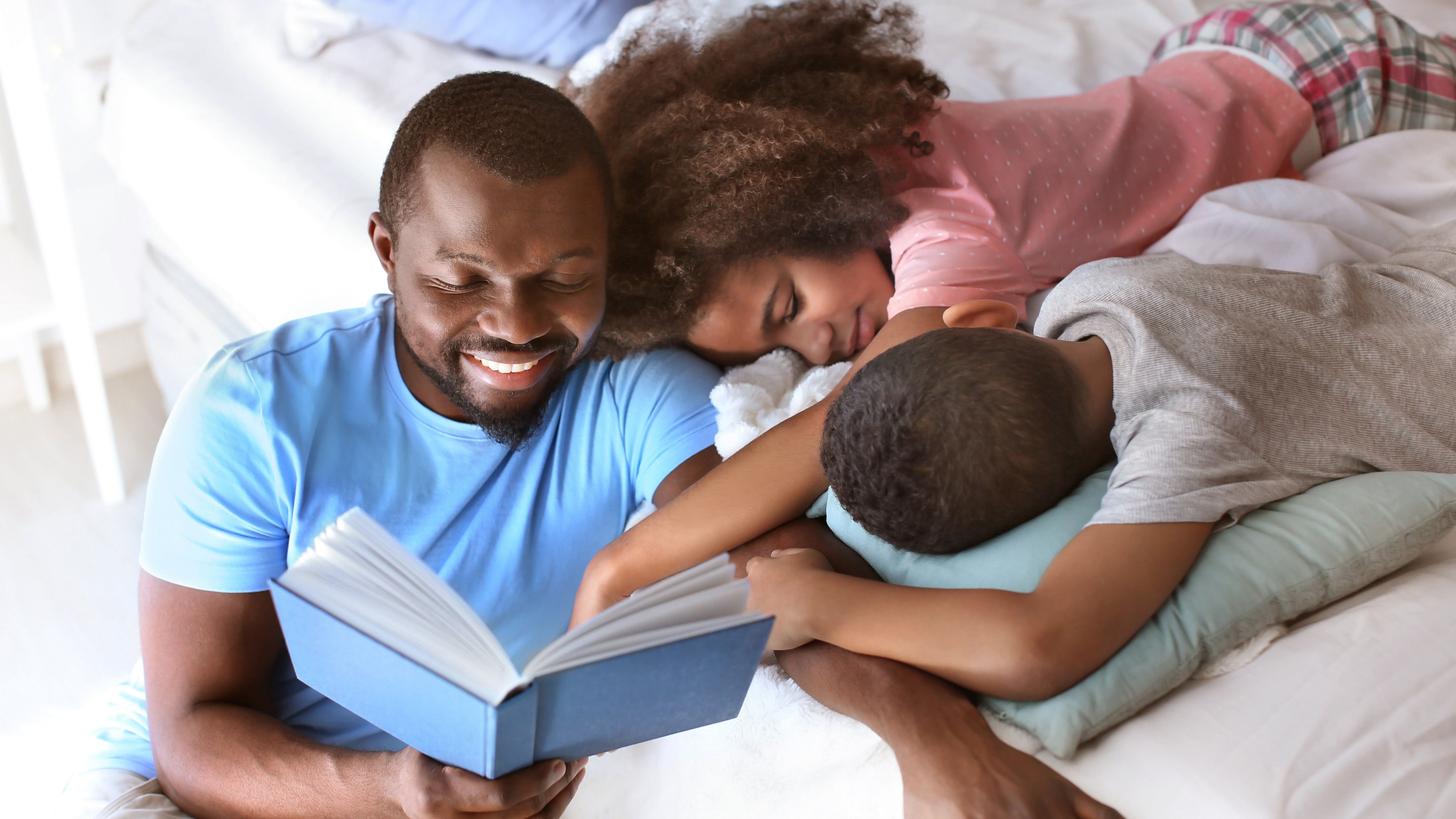 man reading book to boy and girl