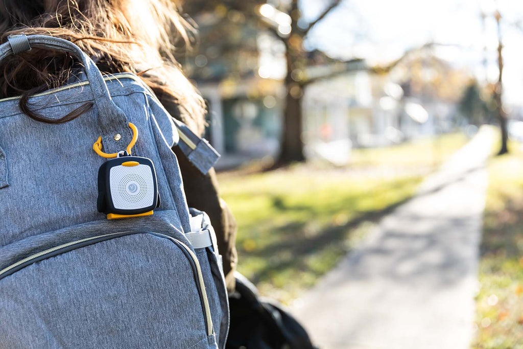 penguin shaped sound machine clipped to a woman's backpack