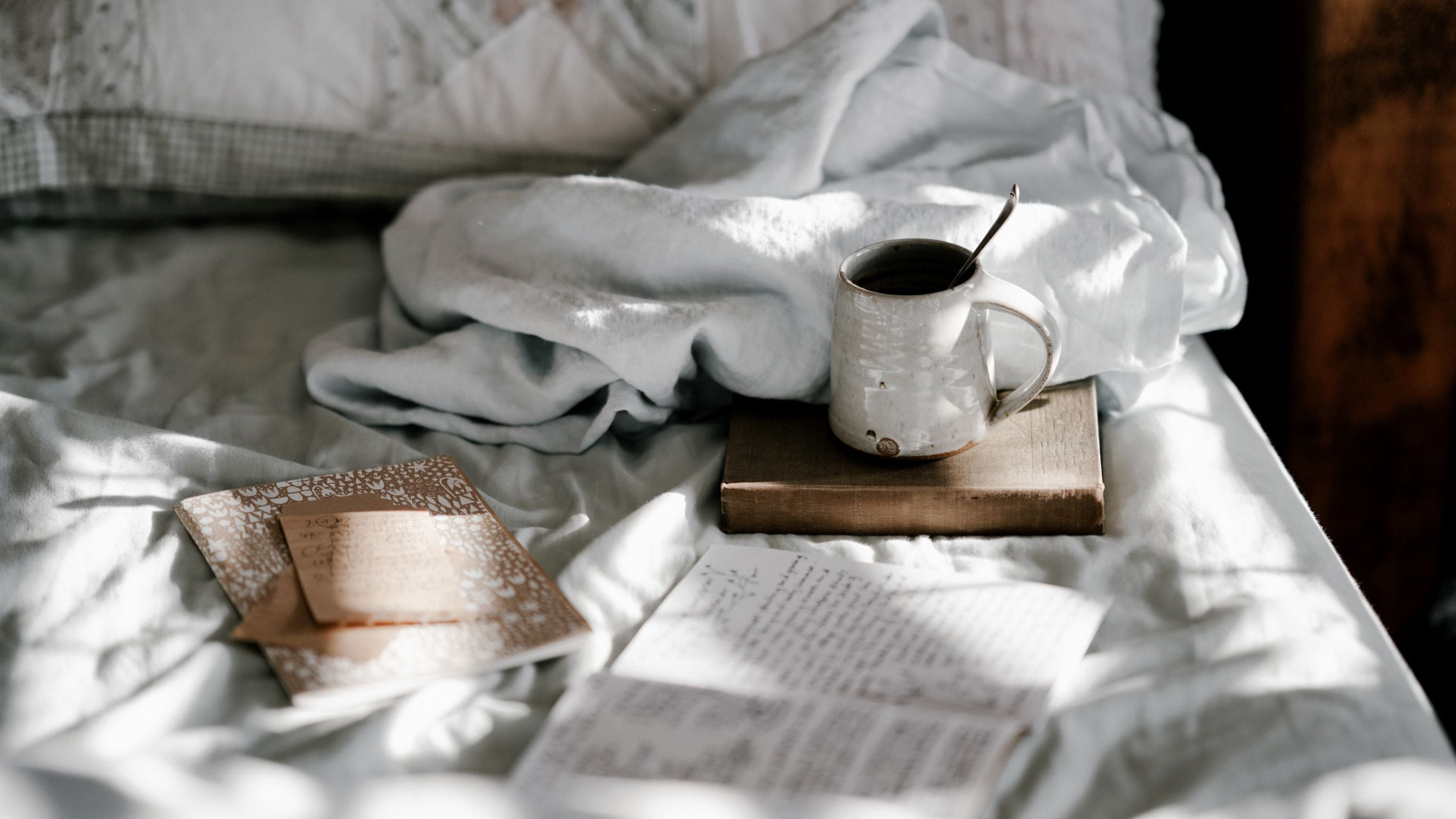 mug on top of bed with journal and books