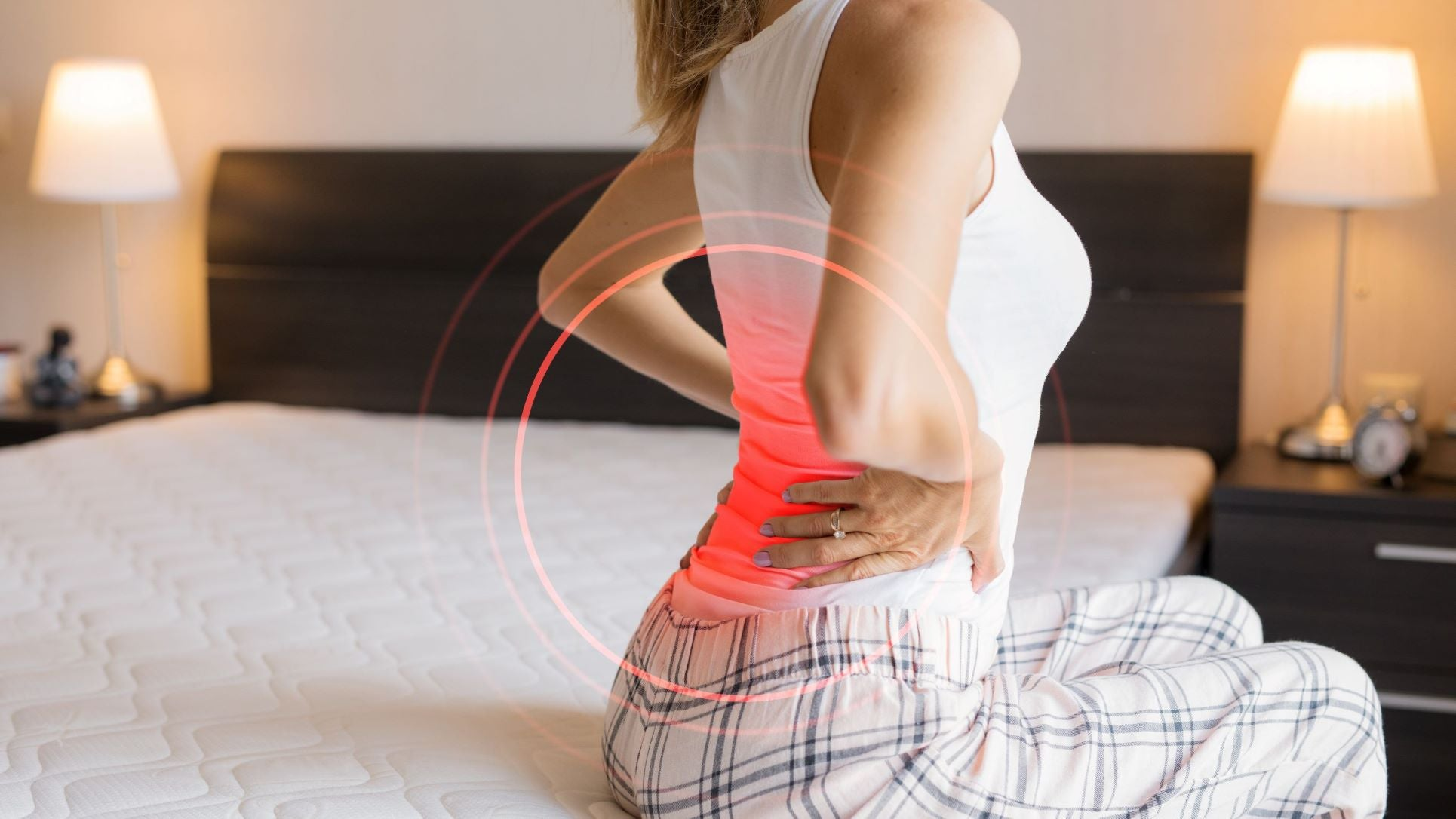 woman sitting on bed back pain