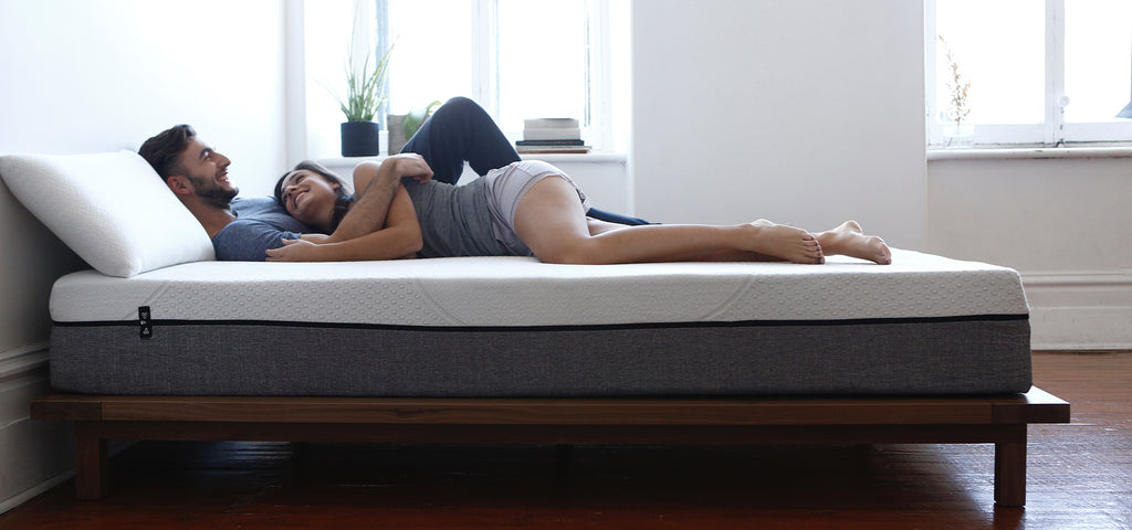man and woman lying on bed and smiling