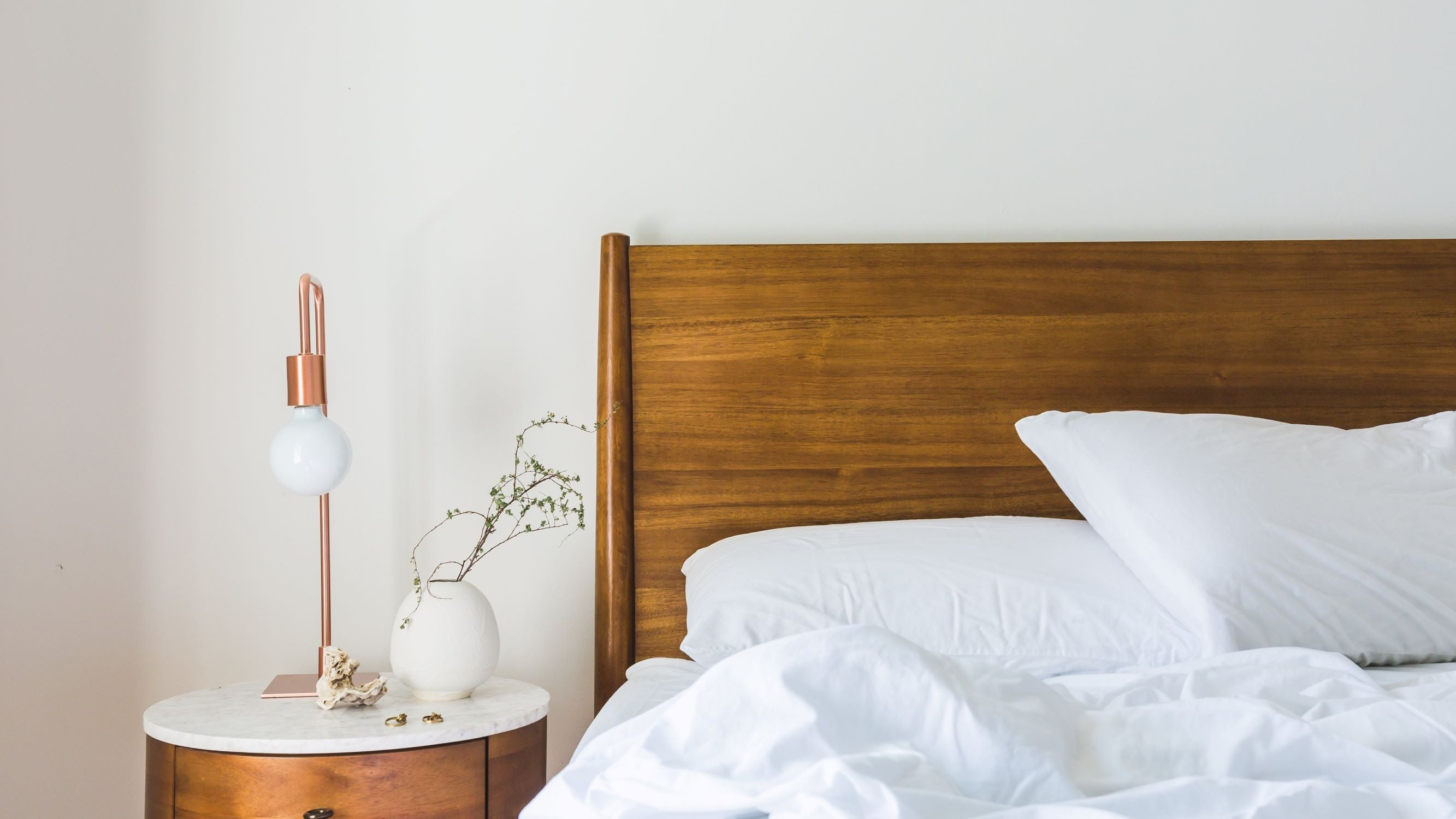 Bed with wooden headboard, white sheets, nightstand with lamp