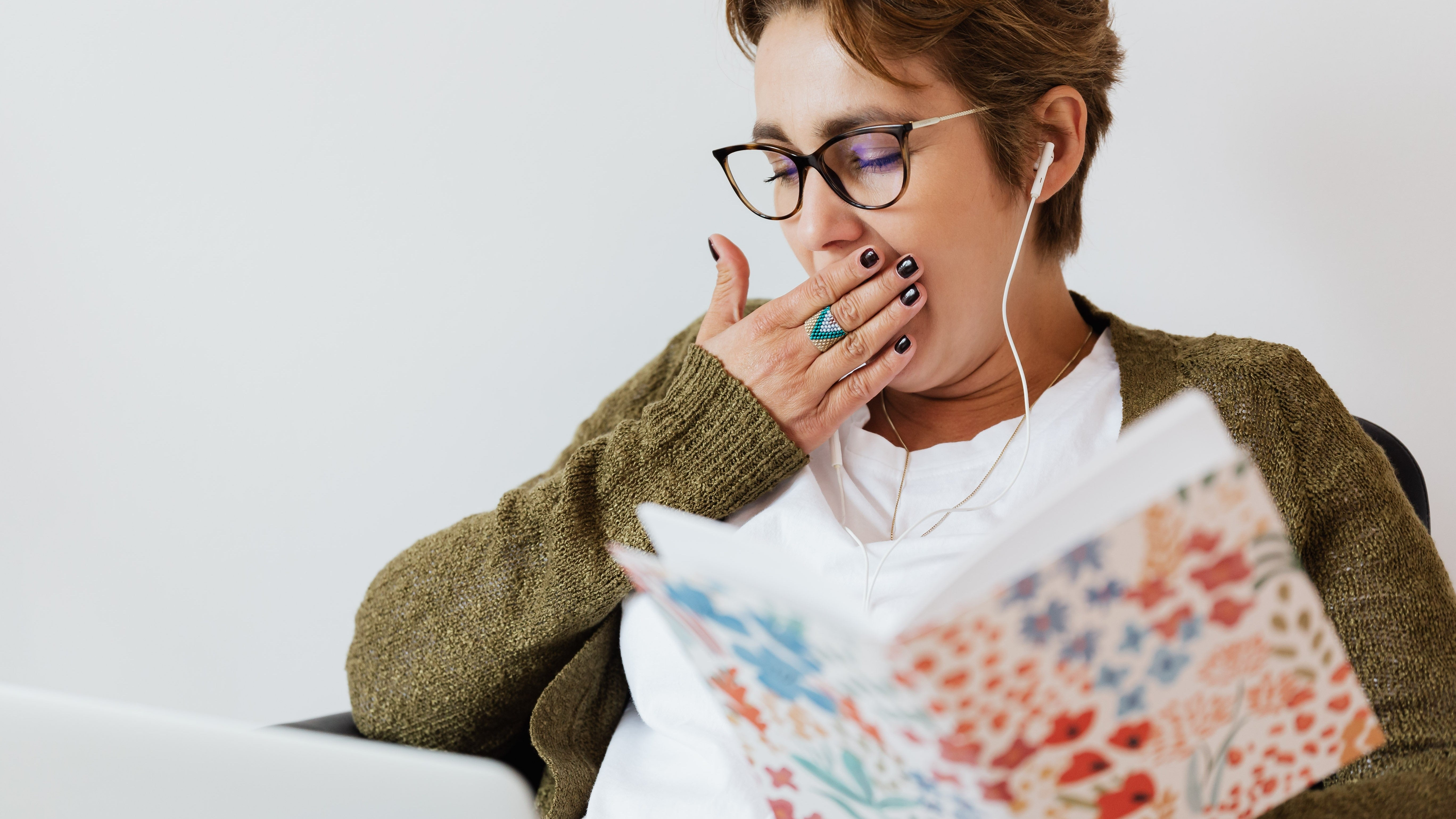 woman wearing glasses yawning and holding a book