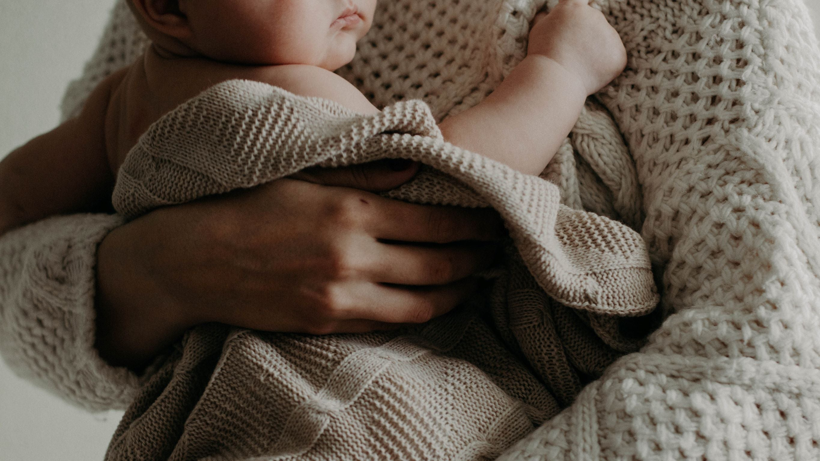 baby being held in cozy blanket by person wearing knit sweater