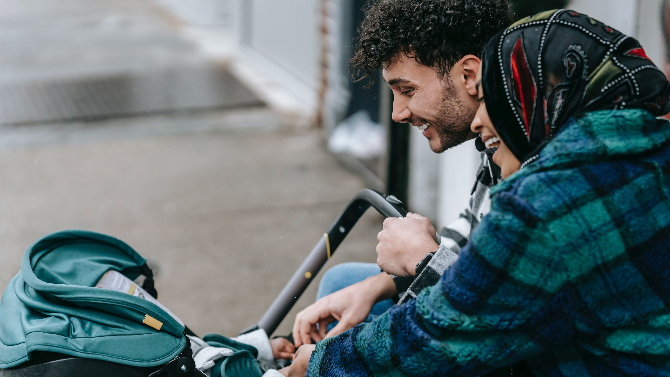 woman and man looking into stroller