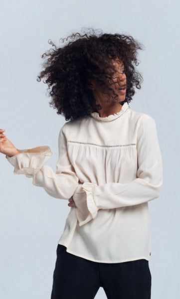 close up of lady wearing smock style cream Frill cuff blouse top - LB Boutique