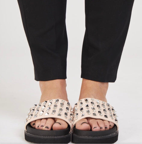 Lady wearing pale pink jewel studded sliders with black sole