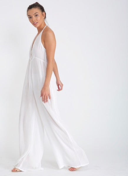 side view of Lady wearing white wide leg hapterneck jumpsuit in cheescloth material - LB Boutique