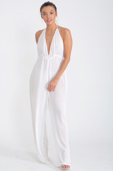 Lady wearing white wide leg hapterneck jumpsuit in cheescloth material - LB Boutique