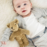 a small organic teddy bear cuddled up to a baby. organic baby toys UK.