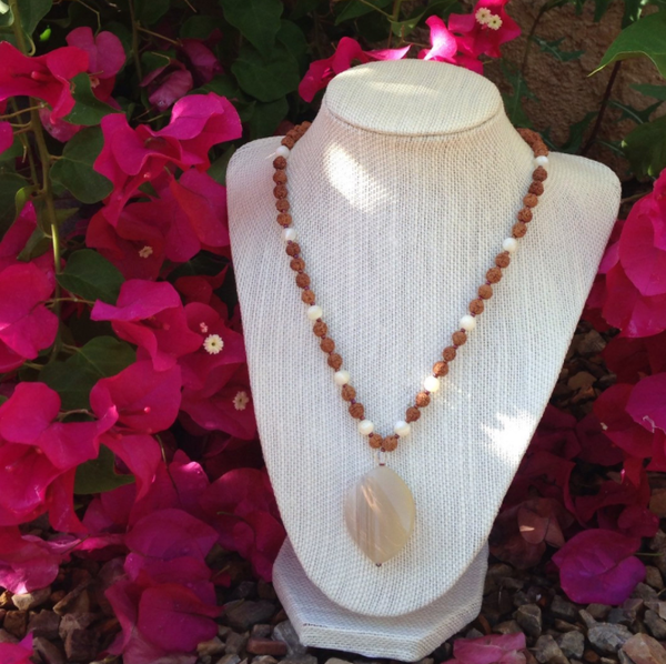 A mala made with onyx, mother of pearl, and rudraksha beads