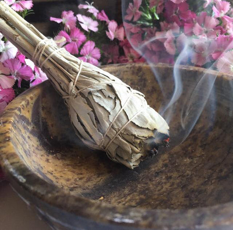 A white sage wand burning