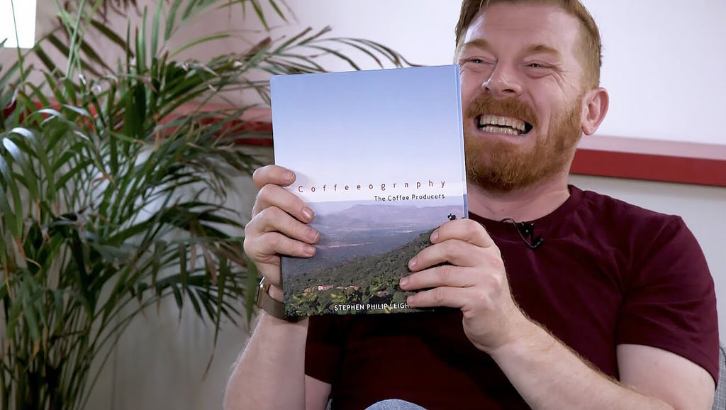 Stephen Leighton holding his new book, Coffeeography