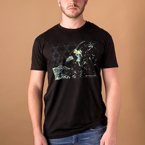 young male wearing black t-shirt with neon image of colorado mushrooms printed on front