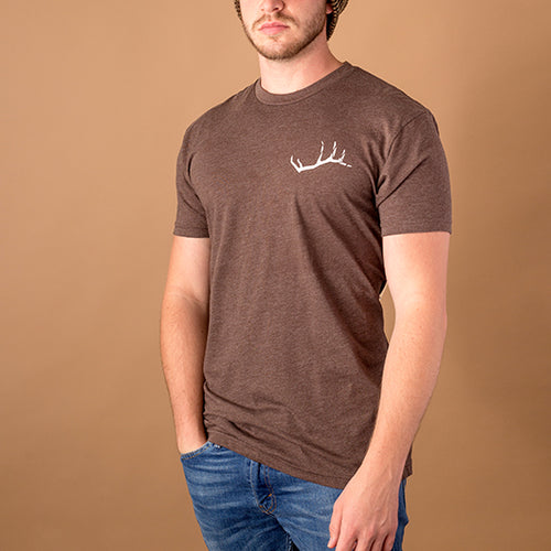 young white male wearing brown t-shirt with small elk antler on upper left breast