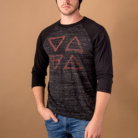 young white male wearing 3/4 sleeve style shirt with black sleeves and marbled black body with image of alchemical  triangle element symbols of earth, air, water and fire print on front