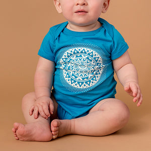 baby wearing bright blue onesie t-shirt with mandala printed in white on front