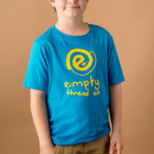 youth white male wearing a bright blue tee shirt with empty thread company logo in yellow with text below that says empty thread co