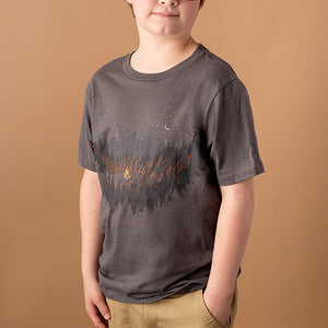 youth male wearing dark grey tee with image of a mountain scene with campfire burning in the center printed on front
