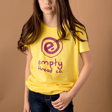 youth girl wearing yellow girls cut tee with empty logo and the words empty thread co printed in purple