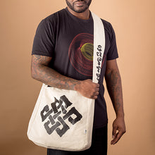 african american male wearing the colorado wire frame design and carrying a cavas market bag with buddhist symol of the endless knot in brush strokes screen printed on it