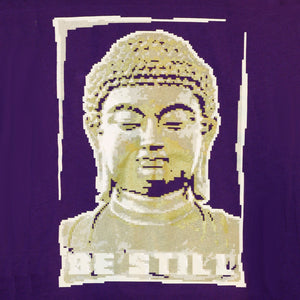 up close of a purple tee shirt with screen printed image of a golden buddha bust in a pixelated style with text below saying be still