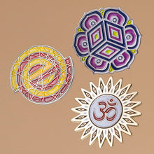 3 enamel pins one of empty logo in red and yellow, one of starburst om design and one of six pedal lotus in purples