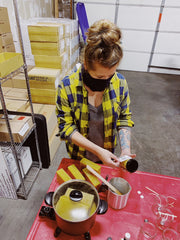 Holly hard at work pouring Limited Edition Pit Liquor beeswax candles.