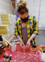 Holly pouring Pit Liquor Limited Edition beeswax candles.